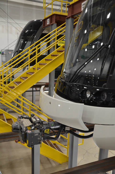 the front end of two trains parked inside, with work areas under the trains for maintenance