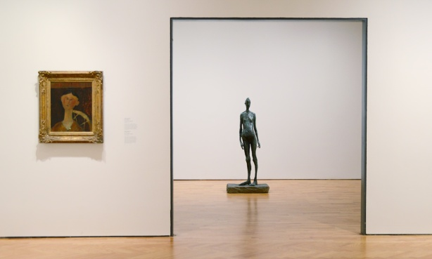 a painting of a woman's head by Modigliano on a gallery wall in a fancy gold frame and a sculpture of a woman in the room beyond