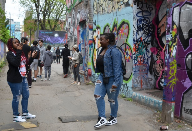 one woman is filming another woman who is talking in graffiti alley