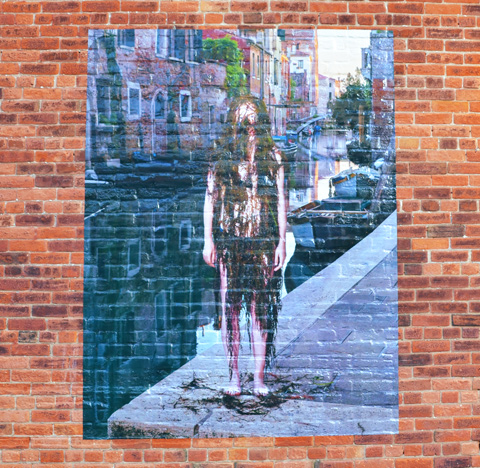 large photo on a brick wall, taken by a canal in Venice, of a woman covered from head to toe in black weeds as she stands beside the canal