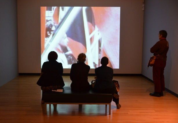 4 people watching a video on a large screen, one person is standing while 3 people are sitting on a bench with their backs to the camera