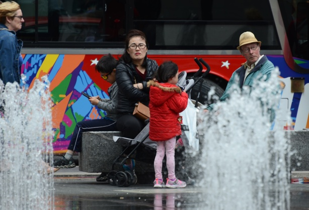 sitting by the water at Dundas square, a mother and two kids, an older man in a hat is nearby