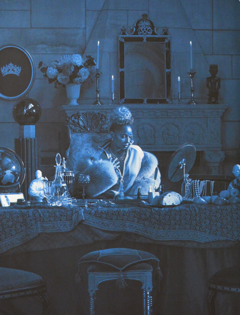 detailed picture of a woman sitting at a table with lots of things around her, on the table, behind her, and in front of the table, by Carrie mae Weems, the photo is only in blues and black