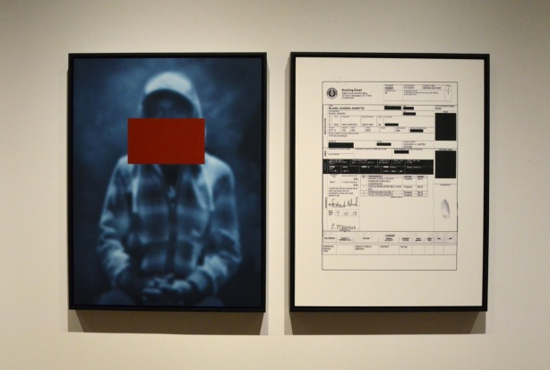 park of an exhibit in a gallery showing the picture of a black boy with a large red rectangle acros his face, beside it is an enlargement of the arrest record of a black man in Ferguson Missouri