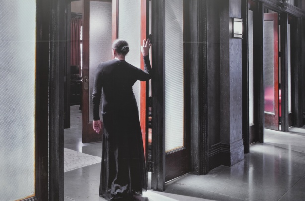 large photo on a wall outside, of a woman in a long black dress, back to camera, one hand on door sill as she stands in open doorway, by Carrie Mae Weems