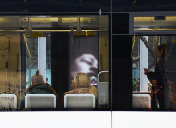 people sitting in a streetcar with their back to the window, can see large photo on exhibit on opposite sidewalk through the windows of the streetcar