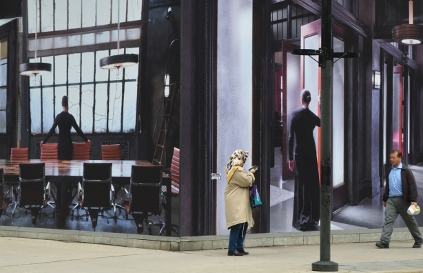 two large photos mounted on two walls that meet at the corner of King West and Widmer, two people walking them including a woman in a head scarf