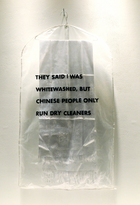 artwork by Florence Yee, a plastic dry cleaners bag hanging on a hanger on a wall with a white fringed piece of cloth inside, on the outside of the bag are the words, They said I was whitewashed by Chinese people only run dry cleaners