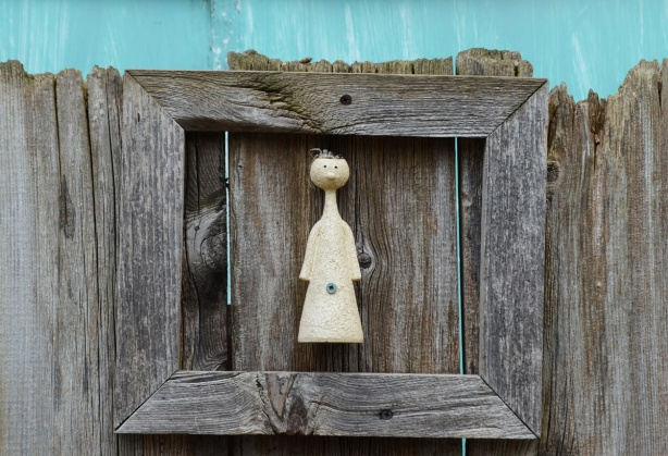 a stylized figurine, round head on conical body, screwed onto a wood fence and surrounded by a wood frame