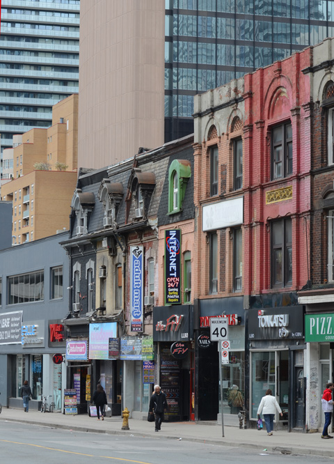 a variety of ages of buildings on Yonge street from those built in the 1800s to modern glass buildings.