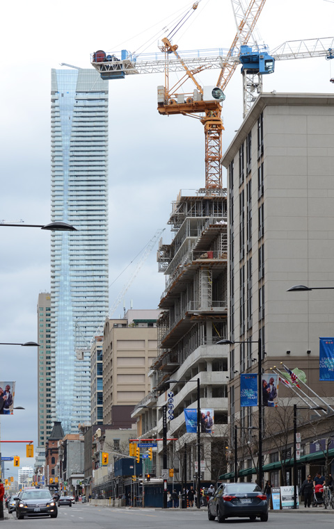 looking north on yonge street towards alexander and bloor. tall buildings, old buildings, cranes, traffic