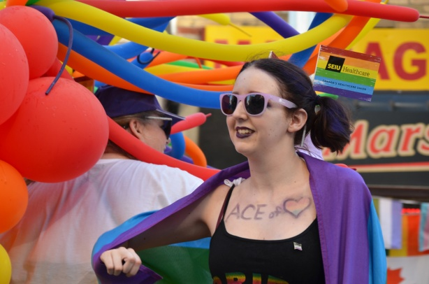 a woman in a low neck black top has Ace of and then a picture of heart on her chest, a pride flag is draped over her shoulders, walking with lots of long tubular shaped balloons