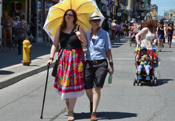 a couple strolls down Yonge St in dyke march, one with cane and large yellow umbrella