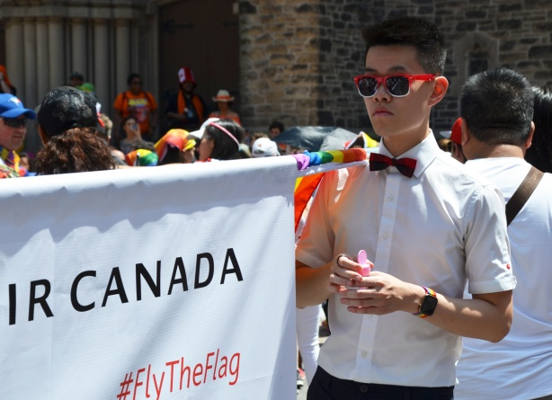 a young asian man in white button down shirt, black pants, black bowtie, and red sunglasses, stands beside an air canada banner, getting ready for pride parade