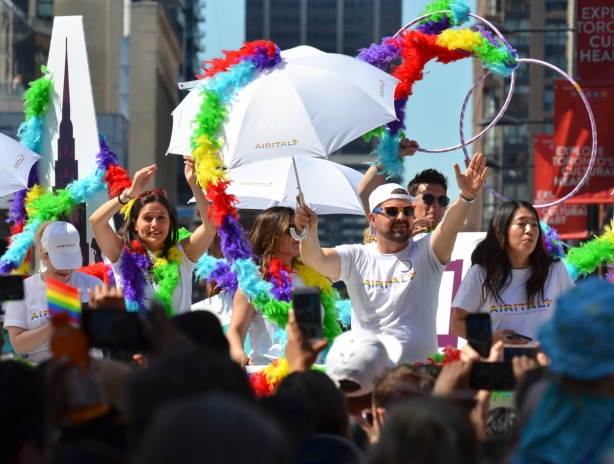 people dressed in white with white umbrellas, on top of a float in the pride parade