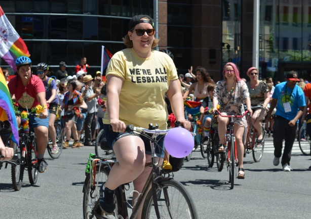 dykes on bikes at start of parade, one is wearing a yellow t shirt that says We're all lesbians