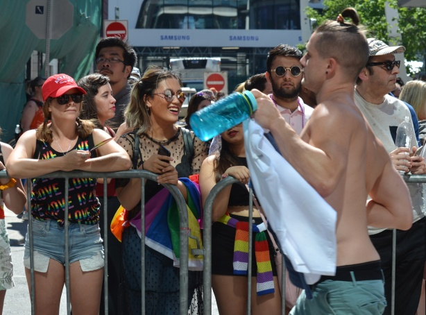 women behind metal barricades at pride parade, as a topless man walks past