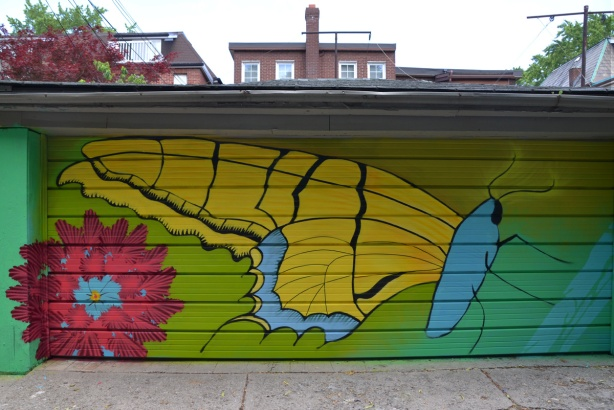 spray painted mural in a lane, large yellow butterfly,