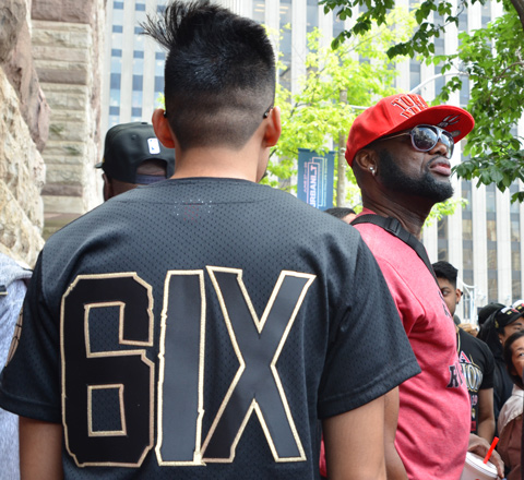 man wearing a black t shirt with 6 ix on the back, walking past a man in red basbeall cap and sunglasses, with black beard