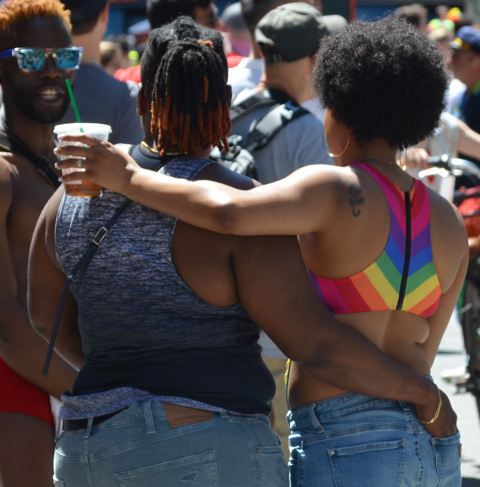 two black women, arm in arm, from the back