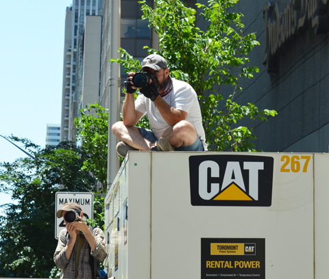 two photographers at a parade, onei s sitting on top of a large generator (trailer)