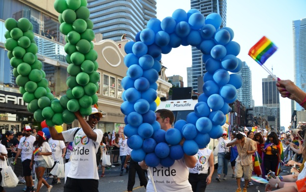two young men in Pride Parade, one has a giant O made of blue balloons and the other is carrying a giant U made of green umbrellas