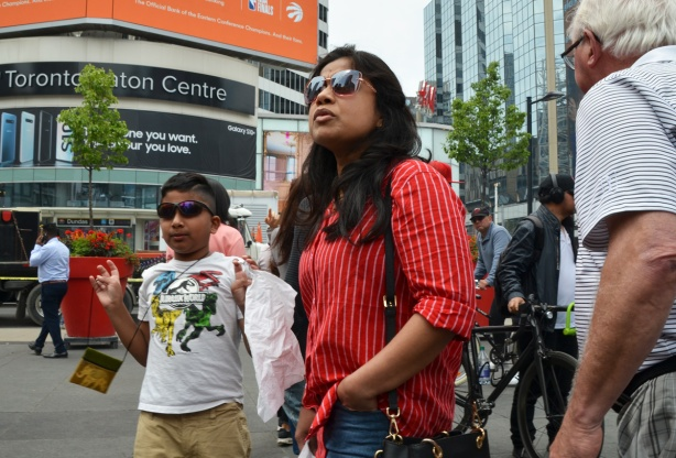 a woman in a red shirt and sunglasses walking with her son who is also wearing sunglasses, south asian ethnicity