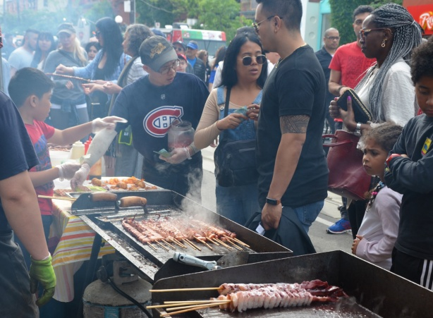 outdoor barbecuing shish kebobs, a boy is cooking and serving, people waiting to buy food