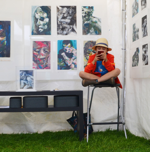 a boy in a fedora sits cross legged on a high stool while looking at a phone. He is in a tent with artwork on the wall that is for sale