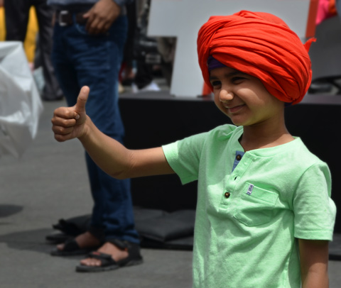 a young boy in a red turban gives a thumbs up sign
