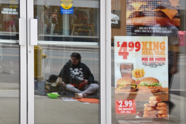 reflection in the glass of a door and window of a Burger King restaurant, of a woman witting on the sidewalk pan handling