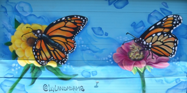 a mural with two monarch butterflys by a flower, bright blue background, garage door