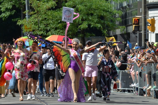 a woman with bright butterfly wings onher arms leads a group of walkers in a pride parade