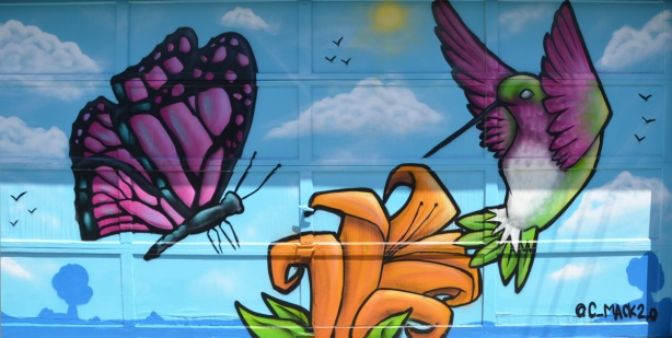 mural on a garage door in an alley, large purple and black butterfly, an orange tiger lily flower and a hummingbird