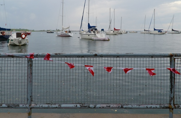 sailboats moored out in Lake Ontario, in the foreground is a metal railing with a string of Canadian flags tied to it