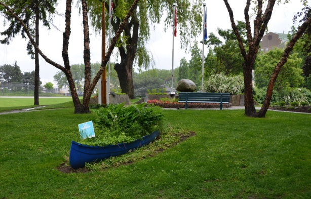 an old blue canoe is used as a planter in a park