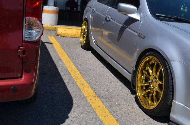 a red van parked beside a silver coloured car with bright gold coloured wheel rims