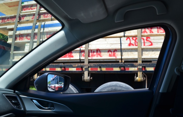 view out the passenger window of a car, of a large flatbed truck loaded with lumber, in the side mirror of the car is the reflection of a TTC bus