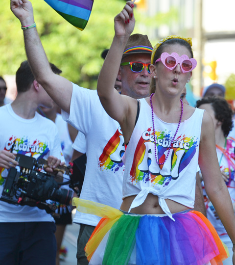 a couple in the pride parade, each wearing white t shirts that say celebrate all, and each with one arm in the air, woman has pink sunglasses and man has rainbow sunglasses and fedora