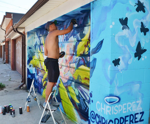 a man on a short ladder spray painting a mural on a garage door in an alley, Chris Perez