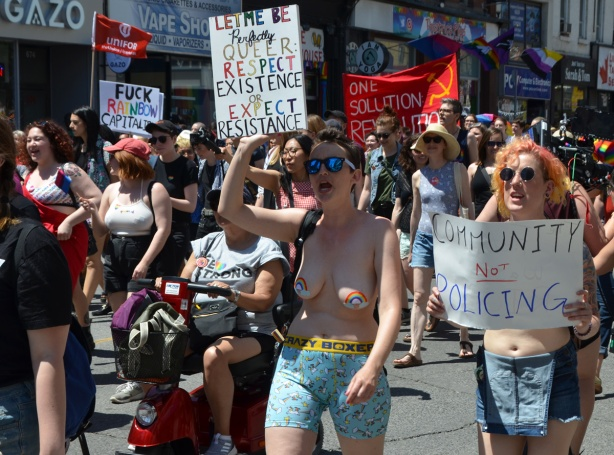 topless woman walking with other women in a dyke march, holding signs and chanting or protesting