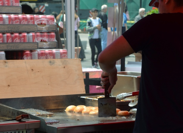 under a tent roof, a man is cooking burgers