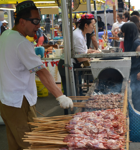a man cooking lamb shish kebob outside at a street festival
