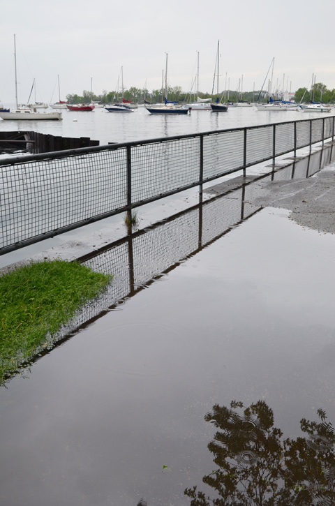 flooded pathway, large puddles, along shoreline at Coronation Park, boats in the background