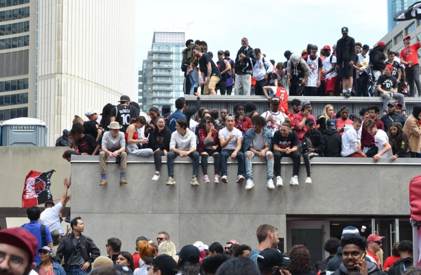 people sitting on top of structures and buildings in front of city hall, Raptors fans celebrating