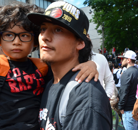 Raptors championship parade day, , a father carries his son, a boy with curlyhair and black glasses