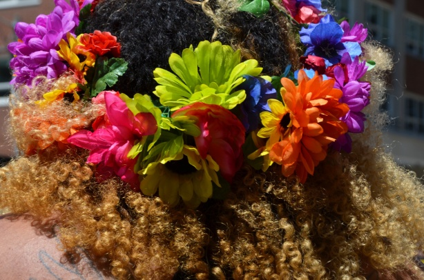 colourful flowers in curly black and brown hair on someone's head, from the back, close up shot