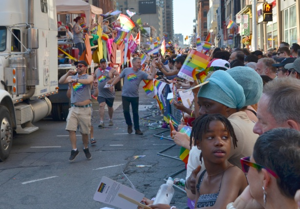 people dancing in the street as they walk beside by the drivers door of a white truck as it pulls a float in the pride parade, going down Yonge street with many people on the sidewalk watching