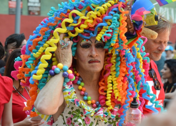 a man dressed in an outfit of big chunky beads in bracelet and necklace and a wig of large coiled bits of plastic in bright colours, many colours,