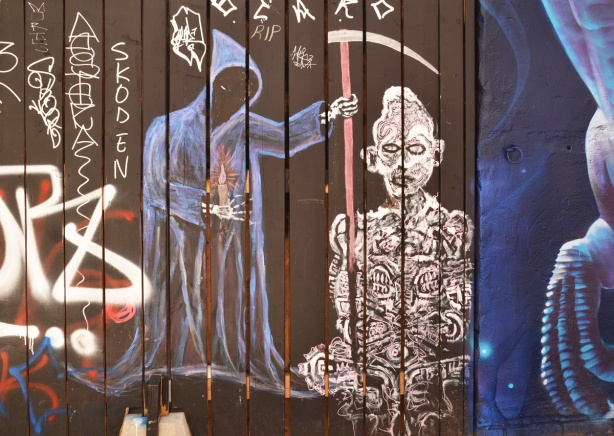 painting on a fence of death with his scythe and holding a candle